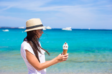 Adorable woman eating ice cream on tropical beach