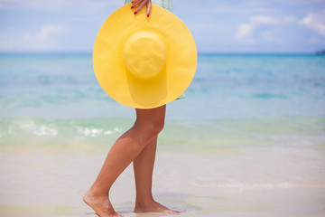 Close up of yellow hat at female hands on beach