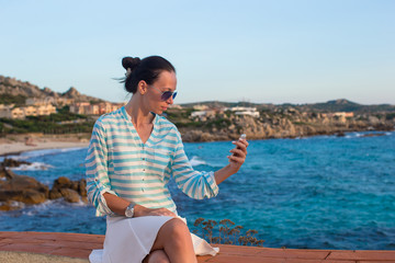 Young woman talking on phone during tropical beach vacation