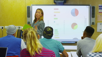 Attractive young teacher in class, explaining a subject to her students.