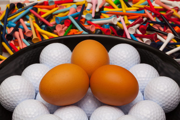 Golf balls and eggs on a black plate