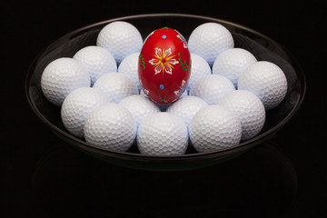 Golf balls and egg on a  black plate