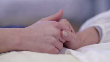 Close up holding the hand of an elderly patient in hospital bed. No faces can be