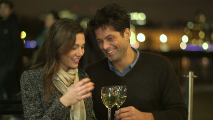Young couple in love drinking wine at an open air terrace in the city
