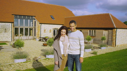 Portrait of happy attractive couple standing outside rural home
