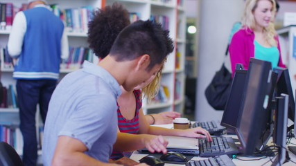 Diverse student group working and studying together in college library.