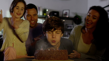 Young boy blows out the candles on his birthday cake
