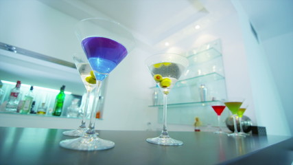 Cocktail glasses filled with a variety of colorful drinks in empty modern bar