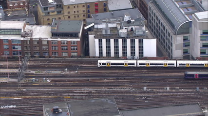Aerial view of passenger trains passing at a London city station