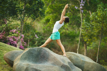 The girl is engaged in yoga on the nature on a large stone