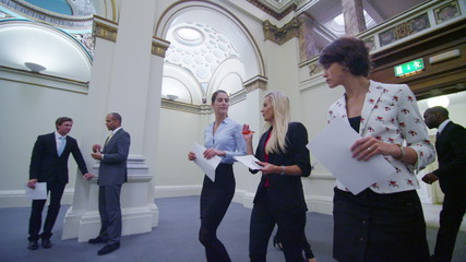 Attractive female business delegates chat as they walk through elegant building