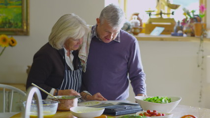 Happy mature couple following a recipe & preparing food together in the kitchen