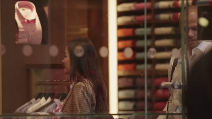 Attractive professional couple shopping together in a man's clothing store