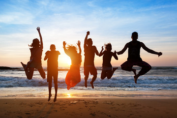 Six people jumping on beach at sunset.