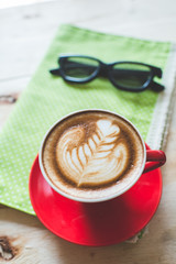 Red coffee latte art cup and glasses on wooden background.