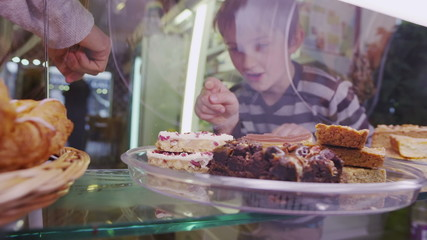 Cute little boy choosing from a selection of fresh pastries in a cafe or bakery