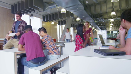 Happy student group working and relaxing together in cafe area of college