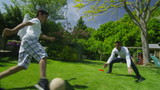 Cute young boy playing sports with his father, in the garden on a summer day