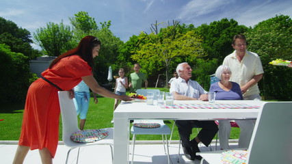 Family and friends of many generations enjoy lunch in the garden on a summer day