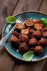 Plate with meatballs over dark wooden background, close-up