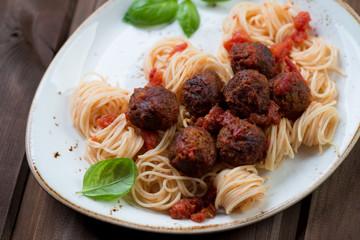 Meatballs with tomato sauce and spaghetti, close-up, studio shot