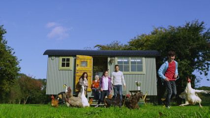 Extended family group outside quaint caravan with chickens and ducks