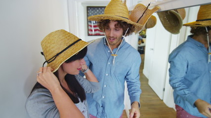 Young happy couple have fun trying on a selection of straw hats.