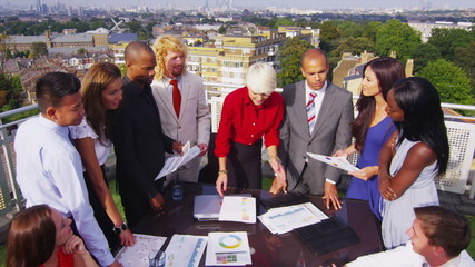 Attractive mixed ethnicity business team in open air meeting with city view
