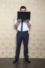 businessman is hiding behind a laptop