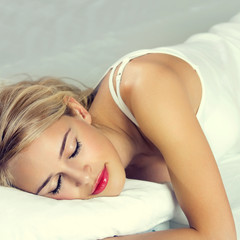 Young blond woman sleeping on bed