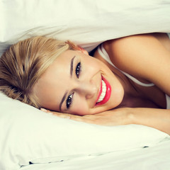 Happy young blond woman waking up