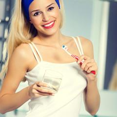 Happy woman brushing teeth