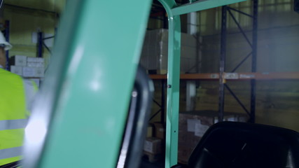 A female forklift truck driver arrives on shift in a factory