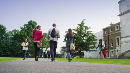 Mixed ethnicity groups of students chat as they walk together around campus