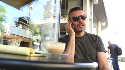 Man uses smartphone in a cafe