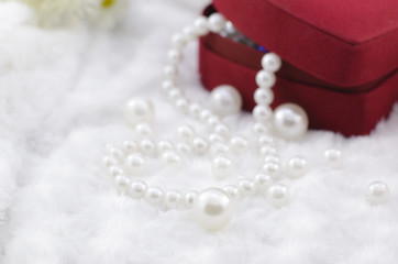 white pearl necklace with red jewel box
