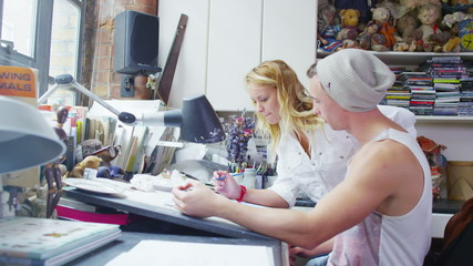 Two young designers or artists collaborating together in their studio