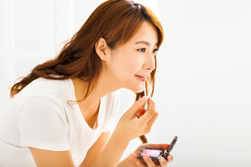 young woman applying lips makeup with cosmetic brush