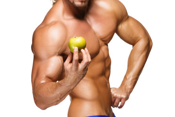 Shaped and healthy body man holding a fresh apple fruit