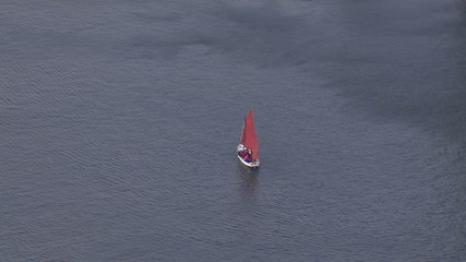 Aerial view of small sailboat and crew sailing on calm waters