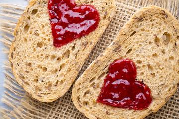 Grain slice of bread with jam heart shape.