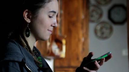 Ragazza sorride mentre scrive un sms con cellulare smartphone