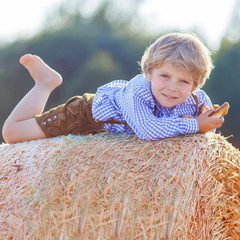 Funny little kid boy lying on hay stack  and smiling