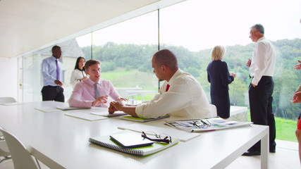 Two young businessmen in discussion in contemporary glass office