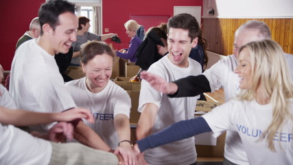 Happy circle of volunteers put their hands together in a show of unity