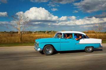 Old classic car on street of Cuba with white clouds and blue sky