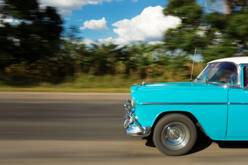 Old classic car on the road in Cuba with white clouds and blue s