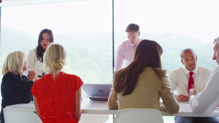 Business team meeting in light contemporary office with natural outdoor views