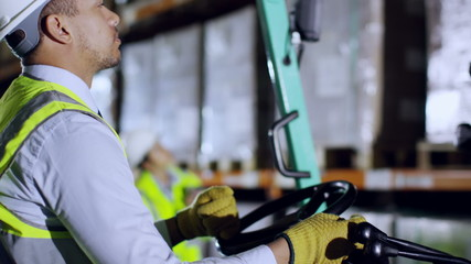 A forklift truck driver and his co-worker are working in a warehouse at night
