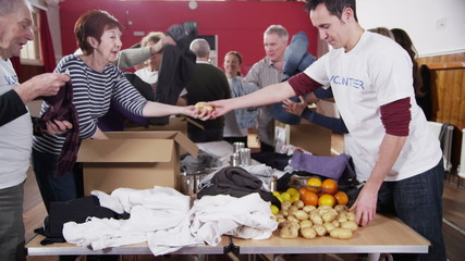 Time lapse of a large group of charity volunteers sorting through donated goods